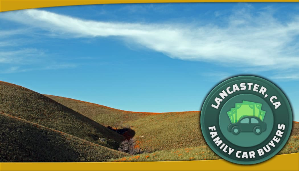 Green Family Car Buyers emblem in front of rolling hills in Lancaster, CA