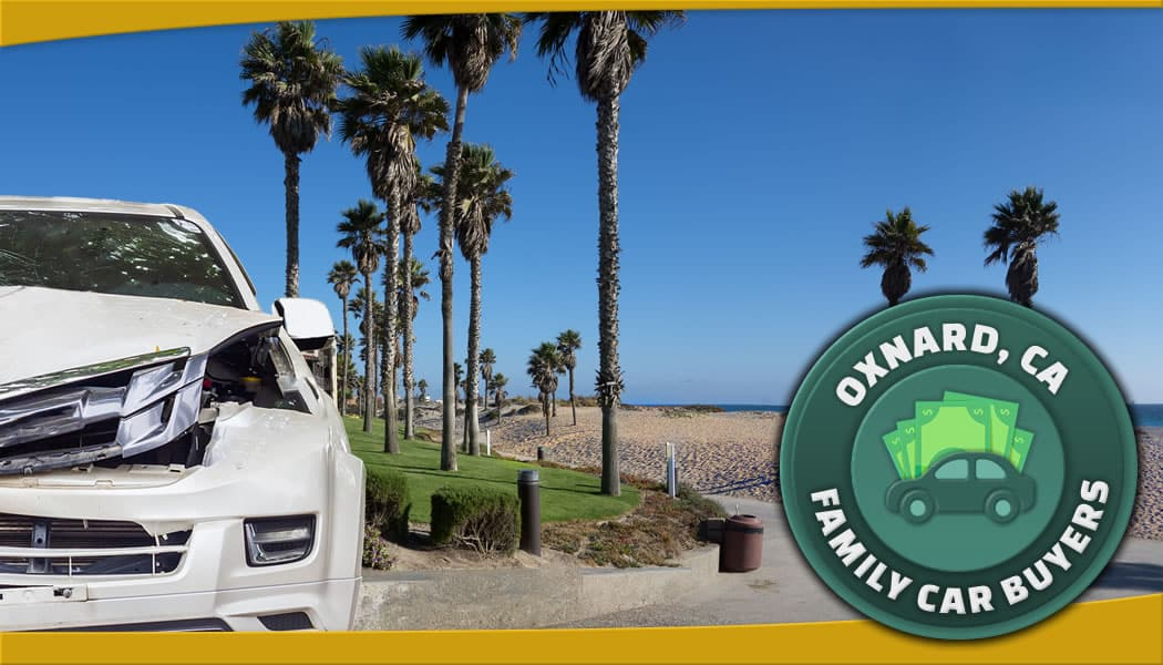 Newer damaged white car in front of the beach along with our FCB emblem