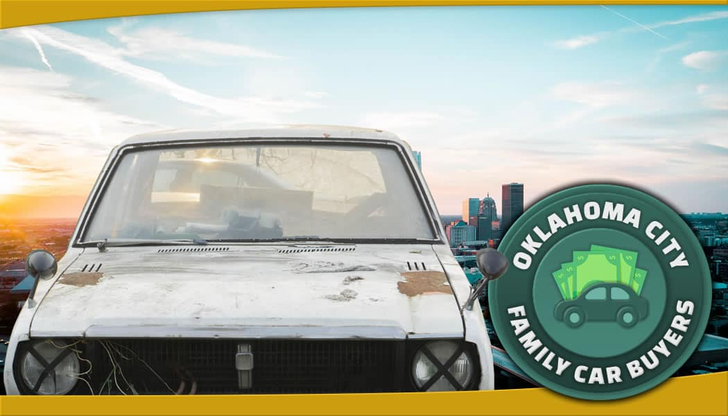 Pale white clunker in front of Oklahoma City daytime along with green FCB emblem