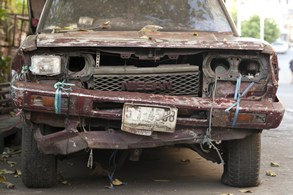 A rusted and damaged truck from the front-end view